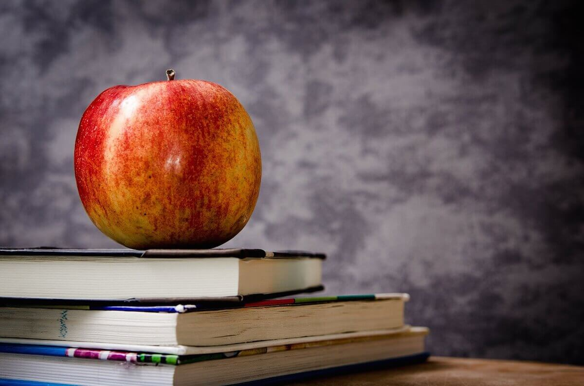 Photo of apple on top of books